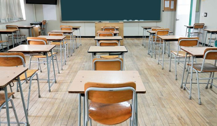 Wooden desks facing a blackboard in an empty classroom.