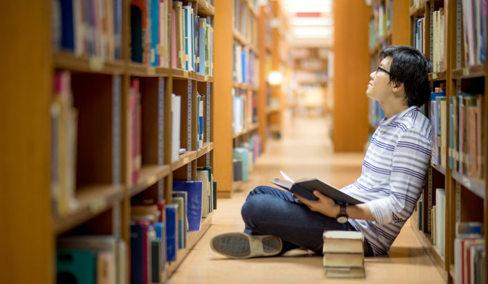 Student looks content while reading books in library stacks.