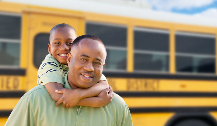 Father and son in front of a school bus
