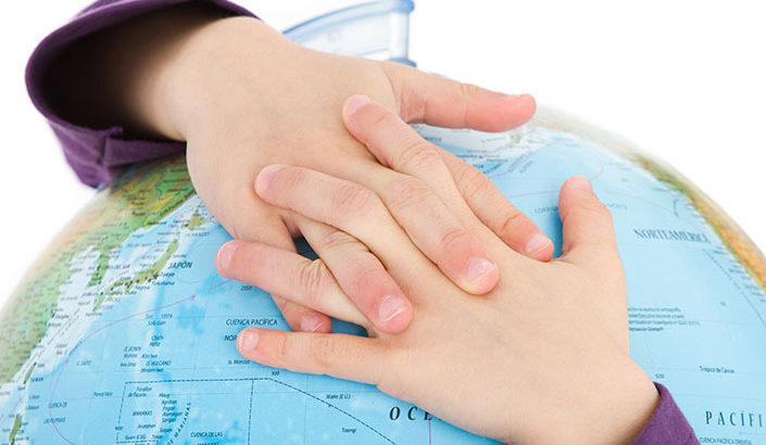 Child's hands hugging a globe