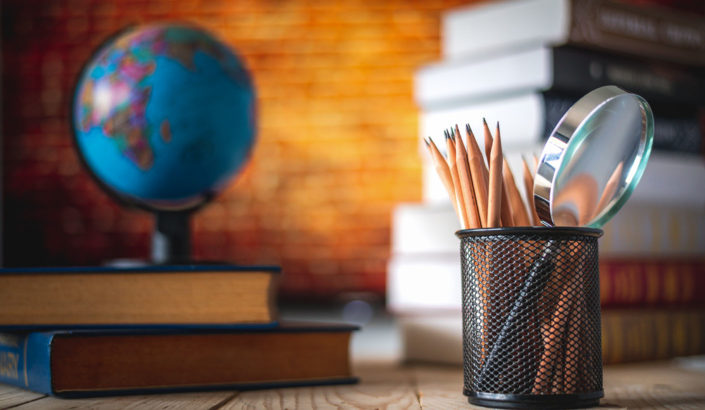 Desk with pens, books and a globe